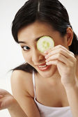 Young Woman Holding Cucumber Slice Over Eye — Stock Photo