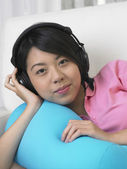 Young woman listening to music on the sofa. — Stock Photo