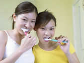 Two ladies brushing teeth together — 图库照片