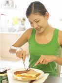 一位年轻女士,用叉子吃早饭的时候 — 图库照片