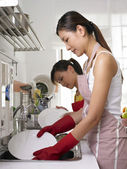 A young lady scrubbing the plate — Stock Photo