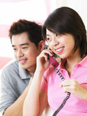 Young man listening to his spouse talking on the phone — Stock Photo