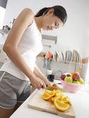 Arance di taglio giovane signora in cucina — Foto Stock