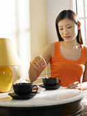 Young woman making cup of tea — Stock Photo
