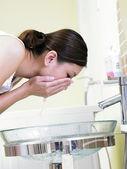Mladá žena mytí obličeje — Stock fotografie