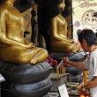 Thailand, Bangkok, Chinatown District, Yaowarat Road, Traimitwitthayaram Temple (Wat Traimit),  a Thai man is offering religious burning sticks to Buddha statues — Stock Photo