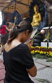 Thailand, Bangkok, Chinatown District, Yaowarat Road, Traimitwitthayaram Temple (Wat Traimit), a Thai girl is praying in front of Buddha statues — Stock Photo