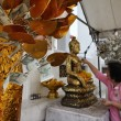 Thailand, Bangkok, Yai District, Arun Temple (Wat Arun Ratchawararam), Thai woman offering flowers to a Buddha statue — Stock Photo