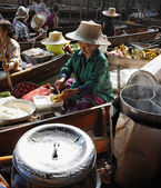Thailand, Bangkok, Thai woman cutting mango fruits on a wooden boat at the Floating Market — Stock Photo