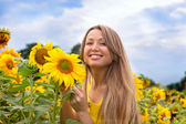 Beautiful woman between sunflowers — Stock Photo