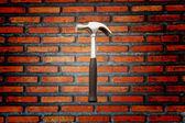 Brick walls and a hammer — Stock Photo
