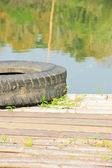 Old tires are put on the bamboo — Stock Photo