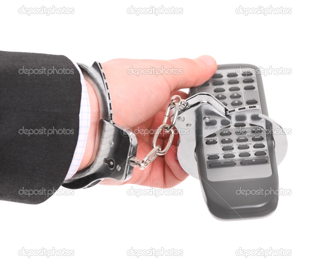 A picture of a male hand chained to remote control over white background — Stock Photo #9715760