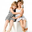 Two little girl friends sitting together isolated on white — Stock Photo