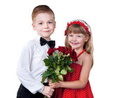 Girl and boy greeting with flowers isolated over white — Stock Photo