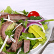 Beef sirloin strips mixed with green salad — Stock Photo