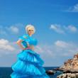 Beautiful young blond girl standing on the beach in a blue dress — Stock Photo #8075416