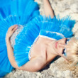 Beautiful young blond girl standing on the beach in a blue dress - Stock Photo