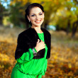 Beautiful brunette in a green dress walks on autumn park — Stock Photo