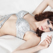 Young girl in a silver dress resting in a hotel — Stockfoto
