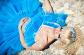 Beautiful young blond girl standing on the beach in a blue dress — Stock Photo