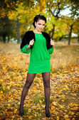 Beautiful brunette in a green dress walks on autumn park — Stock Photo