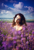 Young beautiful girl in the brown dress in lavender field — Stock Photo