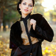 Portrait of the young business woman  in autumn park — Stock Photo