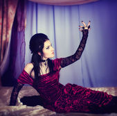 A portrait of the girl in Gothic style on a beautiful bed — Stock Photo