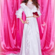 Bride in a white wedding dress on a pink background - Stock Photo