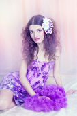 Portrait of the young, beautiful brunette in a lilac dress and w — Stock Photo