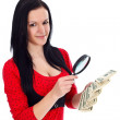 Woman with money and magnifying glass — Stock Photo