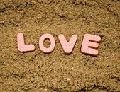 Love sign and sand background — Stock Photo
