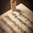 Candle illuminates the music paper — Stock Photo