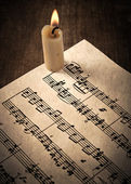Candle illuminates the music paper — Стоковое фото