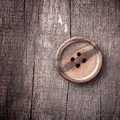 Button on a wooden table — Stock Photo