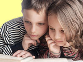 Brother and sister reading a book, on the bed — Stock Photo