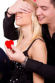 Romantic guy gives girl a red heart — Stock Photo