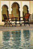 Wooden chairs by a swimming pool against medieval architecture in Udaipur, India — Stock Photo