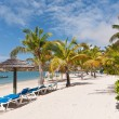 A Sunny Caribbean Beach with Sunloungers and Umbrellas — Stock Photo #10110495