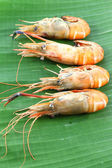 Vertical row of shrimp grilled on banana leaf. — Stock Photo