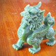 jade chinese sacred animal (call in chinese is pe-sia) on wood background — Stock Photo
