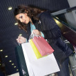 Beautiful woman at the shopping center with bags — Stock Photo
