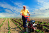 Man works in the field with help of the motor cultivator — Stock Photo