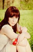 Linda jovem sentado na grama com uma maçã na mão — Fotografia Stock