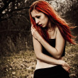 Stock Photo: Portrait of beautiful redhead sad girl among the autumn trees