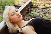 Closeup portrait of beautiful young girl lying on rails — Stock Photo