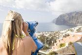 Woman looking through telescope at sea — Stock Photo