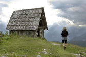 Woman walks to abandoned mountain cottage — Stock Photo