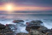 Hermosa playa rocosa en la puesta del sol — Foto de Stock